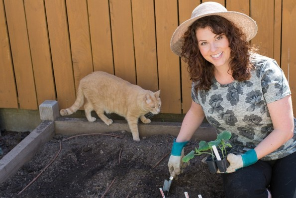 Sarah Lappe works in her garden. Dexter the cat tries to help resize